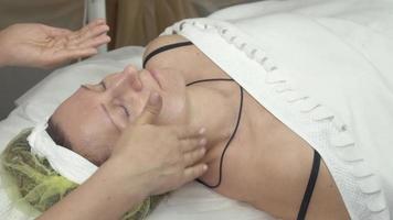 Kosmetikerin legte Feuchtigkeitsöl auf erwachsene Frau Gesicht von Händen in Schönheitssalon