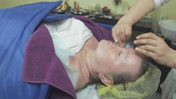 cosmetologista faz massagem de nariz e testa em uma mulher adulta gorda em um salão de beleza