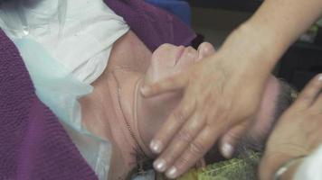Kosmetikerin schmiert Creme auf erwachsenes Frauengesicht im Schönheitssalon. Anti-Aging-Pflege