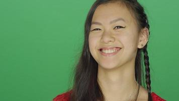 Young Asian woman smiling and being playful, on a green screen  video