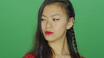 Young Asian woman staring and looking sexy, on a green screen  video