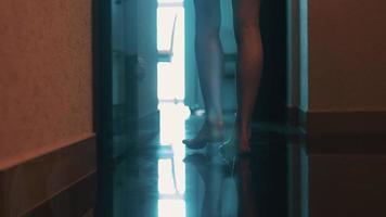 vue de la femme élégamment marcher dans la salle de bain dans l'appartement. porte ouverte. sol. en marchant