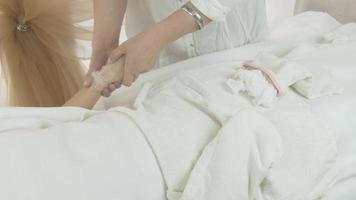 la massaggiatrice ha messo fuori il guanto bianco dalla mano della donna nel salone di bellezza. maschera termica per le mani