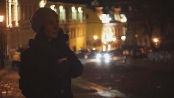 Frau auf der Straße des Abends trinkt Kaffee und telefoniert video