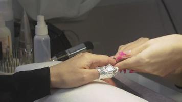 professioneller Manikürist wickelt Nägel der Frau durch Folie im Schönheitssalon ein. Nagelschellackentfernung
