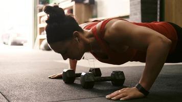 eine fitte junge Frau, die Liegestütze macht und Musik in einem kleinen Fitnessstudio hört