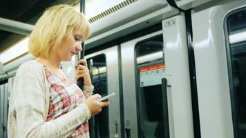una giovane donna che legge un messaggio al telefono, andando in metropolitana. in piedi vicino alla porta il carro