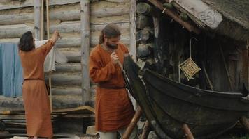 vida de la población civil en el pueblo. vestido con ropa medieval, el hombre hace un barco mientras la mujer cuelga la ropa. Recreación medieval. video