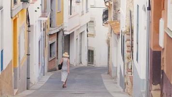 mulher turista com vestido leve e chapéu desce as ruas estreitas da antiga cidade mediterrânea, na Espanha. turismo na europa video
