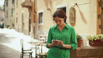 aantrekkelijke jonge brunette vrouw in lichte zomerjurk op straten van Europese stad. ze kijkt naar haar mobiele telefoon en gebruikt die.