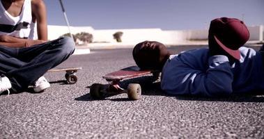 longboarder adolescente sentado e deitado em seus longboards