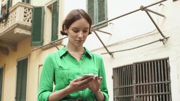 jovem morena atraente com vestido leve de verão nas ruas de uma cidade europeia. ela está olhando para o celular e usando-o.