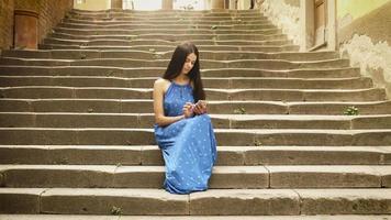 atraente jovem morena com vestido de verão leve, sentada nos degraus das escadas da cidade europeia. ela está olhando para o celular e usando-o.