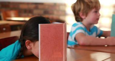 süße Schulkinder, die Globus in ihrem Klassenzimmer lesen und betrachten