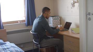 männlicher Student, der im Schlafzimmer der Campusunterkunft arbeitet