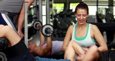 Trainerin hilft dem Mann, seine Crunches zu machen video