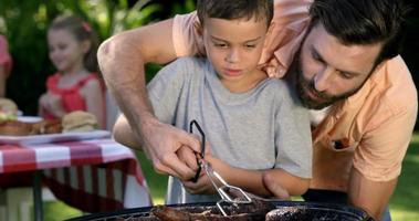 primo piano su un padre sta insegnando a suo figlio a fare un barbecue