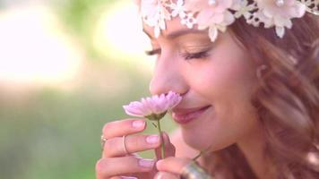 Girl in boho style smelling a fresh flower in nature video