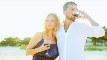 um casal bebendo vinho na praia ao pôr do sol video