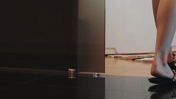 Vue de la jeune fille en pantoufles à pied de la salle de bain et s'asseoir sur une baignoire blanche