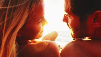 casal deitado em uma praia e olhando para o oceano ao pôr do sol