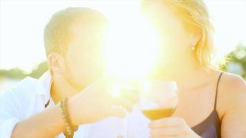 A couple drinking wine on the beach at sunset