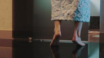 ragazza in accappatoio camminare in bagno in punta di piedi, sedersi sulla vasca. Accendi la luce
