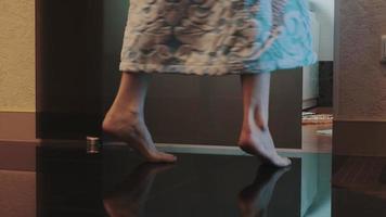 ragazza in accappatoio camminare in bagno in punta di piedi e sedersi sulla vasca. Accendi la luce