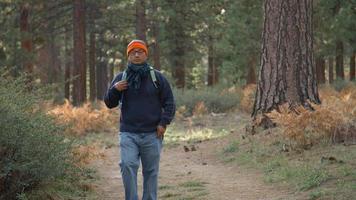 homem asiático usando seu smartphone em uma floresta, vista frontal