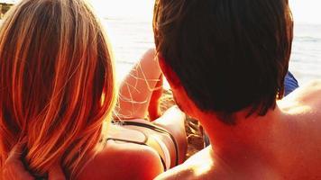 couple allongé sur une plage et vue sur l'océan au coucher du soleil