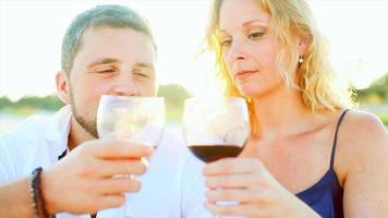 pareja bebiendo vino en la playa al atardecer video