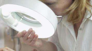 Nahaufnahme Kosmetikerin schauen Mädchenhand in kosmetischer Lupe im Schönheitssalon
