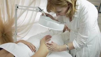 Kosmetikerin untersucht Mädchenhand in Lupe im Schönheitssalon. mittlerer Schuss