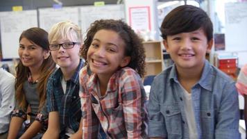 Toma panorámica de niños de quinto grado y maestros en el aula. video