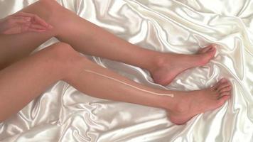 mani che applicano la crema sulla gamba.
