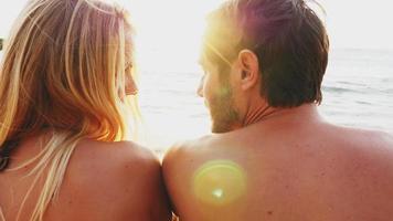 Paar liegt am Strand und schaut bei Sonnenuntergang über den Ozean video