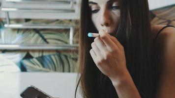 junges Mädchen, das im Badezimmer mit Smartphone sitzt. Rauchen der elektronischen Zigarette