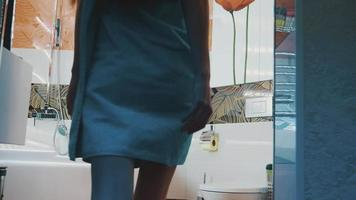 giovane ragazza in asciugamano blu a piedi in bagno aprendo il rubinetto dell'acqua. toccare l'acqua