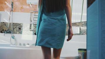 giovane ragazza in asciugamano blu a piedi in bagno aprendo il rubinetto dell'acqua. fare il bagno