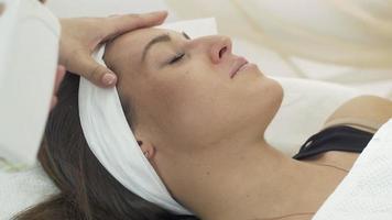 Gros plan des mains de cosmétologue mettre de la cire sur les joues de fille dans un salon de beauté