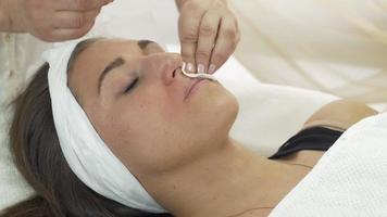 Cosmetóloga profesional limpie por encima de los labios de la niña con una servilleta en salón de belleza