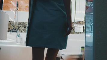 giovane ragazza in asciugamano blu entrare nel rubinetto dell'acqua di apertura del bagno. fare il bagno
