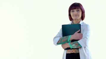 Doctora abrazando una carpeta negra y mirando a la cámara, riendo