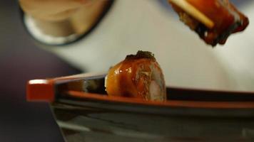 rollos de sushi en un plato oscuro. video