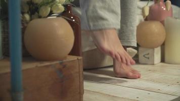 matin, de beaux pieds féminins descendent sur la pointe des pieds du lit