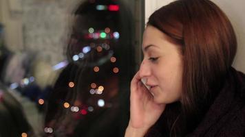 garota senta no parapeito da janela e se despede no telefone video