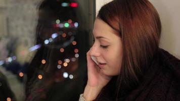 garota sentada no parapeito da janela falando no telefone video