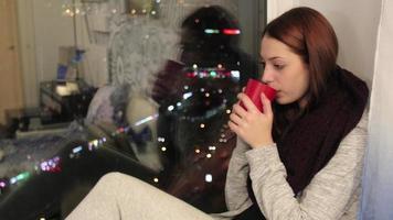 garota senta no peitoril da janela e bebe chá quente na xícara video