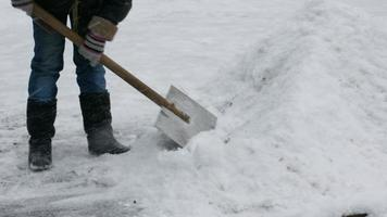 Janitor cleans snow of shovel.