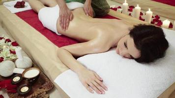 client brune recevant un massage corporel au club de spa